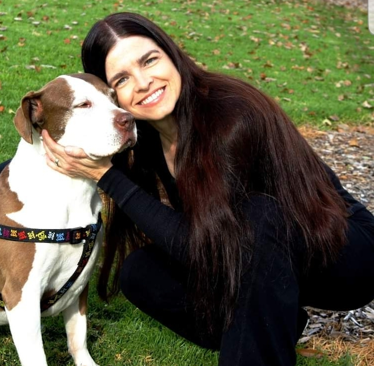 long haired woman hugging pitbull